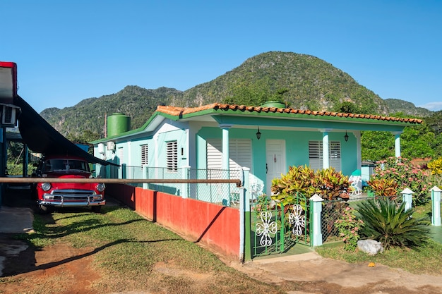 Old fashioned vintage car by the summer colorful house against mountains in the town of vinales, cuba.