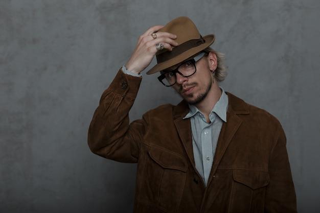 Старомодный хипстер молодой человек с бородой поправляет стильную шляпу в комнате у серой стены.