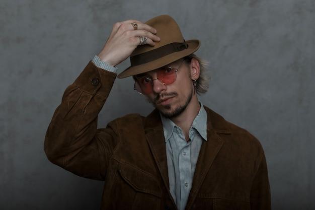 Старомодный молодой человек с бородой в круглых винтажных очках в коричневой модной куртке в классической рубашке стоит и поправляет стильную шляпу в комнате у серой стены. симпатичный парень.