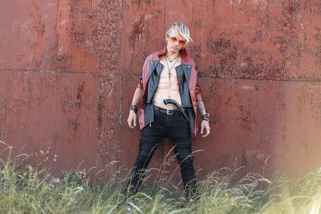 明るい夏の日にさびた壁の近くでポーズをとる古い武器を持ったジーンズの赤黒の革のジャケットの眼鏡をかけた金髪の昔ながらの若い男。屋外で裸の胴体を持つ男
