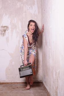 笑顔でラジオを聞いている昔ながらの若い女性