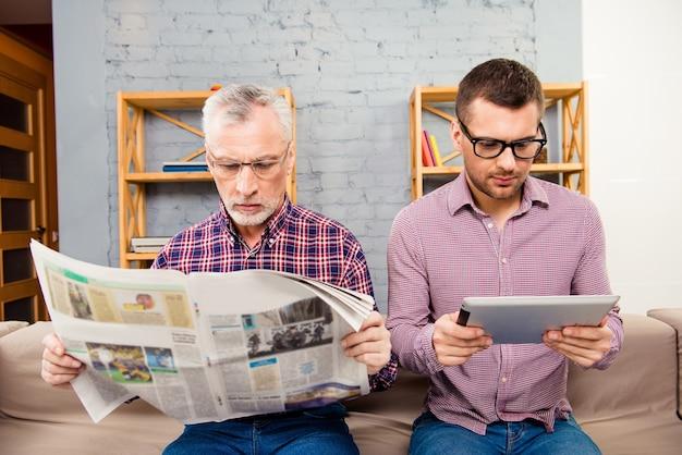 Старый отец читает газету и его сын с помощью планшета