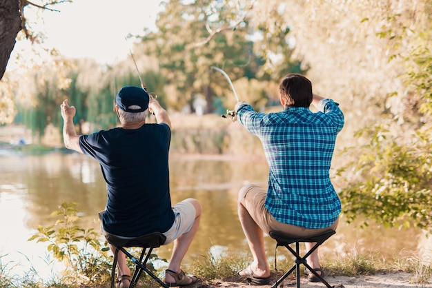 Старый отец с бородатым сыном рыбалка на реке.