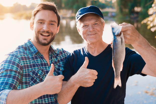 Old father with bearded son fishing on river.