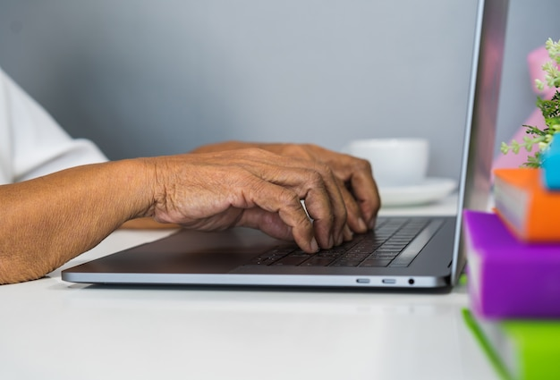 Old female hands typing on laptop keyboard
