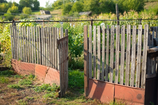 Old fence on a farm in the village. open gate