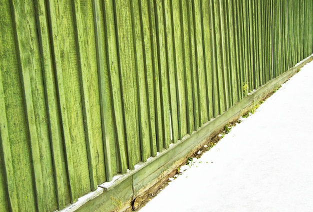 Old fence with cracked green paint wooden background texture