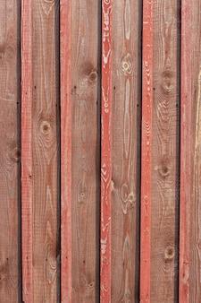 Старый забор с выцветшими красными досками и множеством сучков