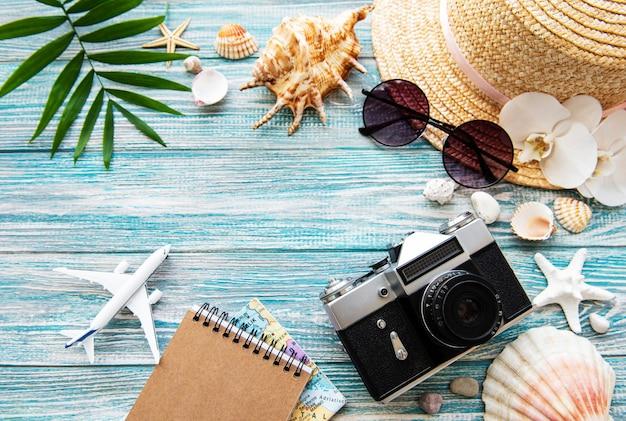 Старая пленочная камера, шляпа, ракушка и пальмовые листья на синей деревянной поверхности