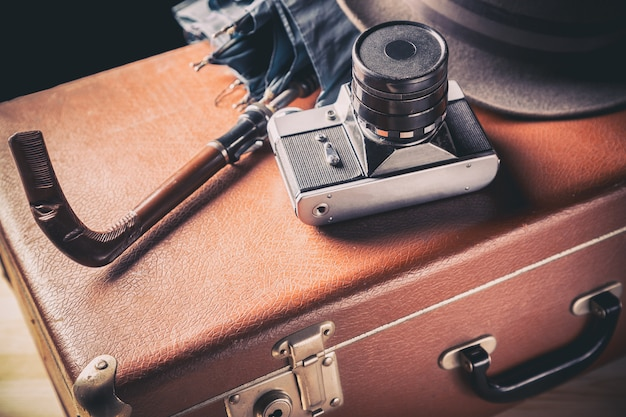 Old film camera with vintage hat and umbrella on old brown suitcase