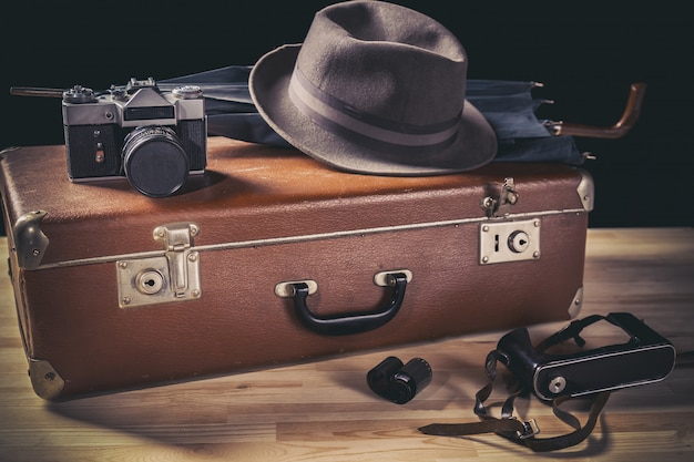 Old film camera with vintage hat and umbrella on old suitcase neat film and camera case