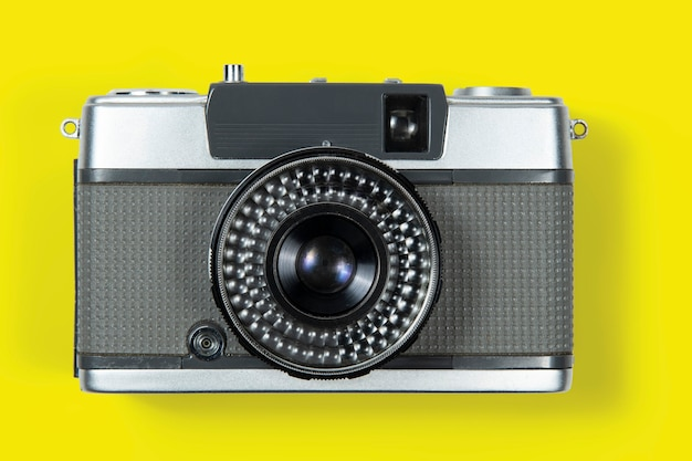 Old film photography camera on yellow background