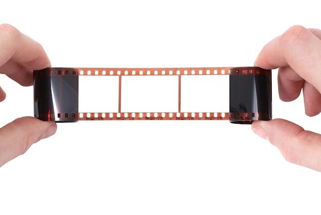 白い背景の上の手に空のフレームを持つ古いフィルム