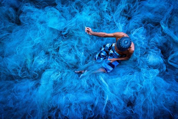 地面に座って青い漁網を縫う老人の手