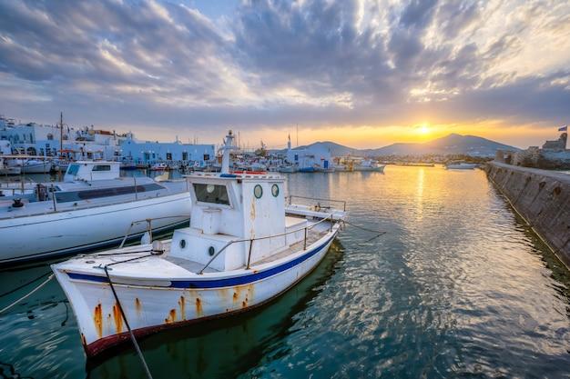 日没のナウサ港の古い漁船。パロス島、ギリシャ