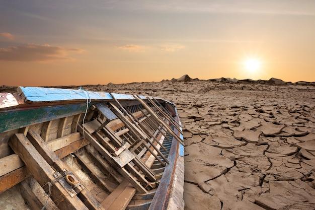 Старая рыбацкая лодка на сухой потрескавшейся земле.