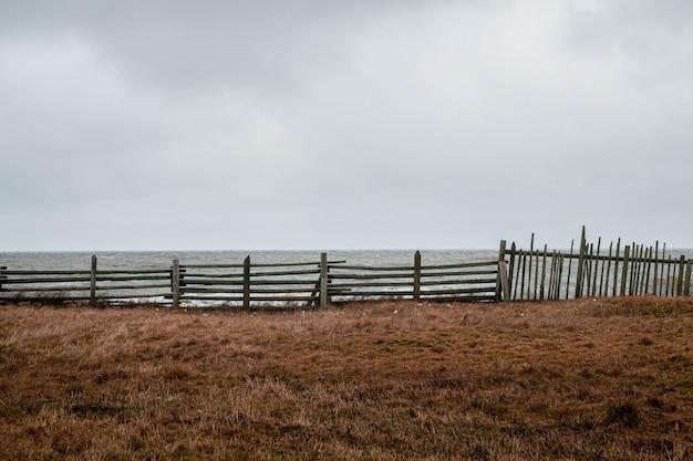 해변에서 극적인 하늘에 오래 된 낚시 울타리.