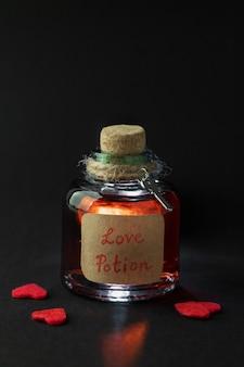 黒の背景に赤いハートのファンタジー愛のポーションと古いフラスコ