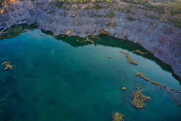 Old flooded stone quarry with large stones in the evening warm bright light covered with small dry plants in picturesque ukraine. aerial panoramic drone shot