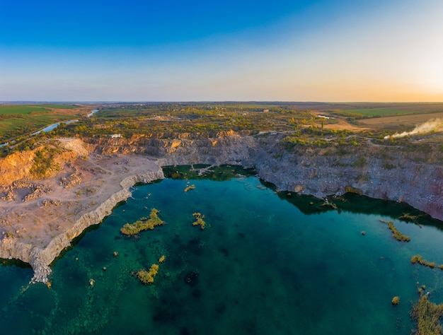 Old flooded stone quarry with large stones in the evening warm bright light covered with small dry plants in picturesque ukraine.