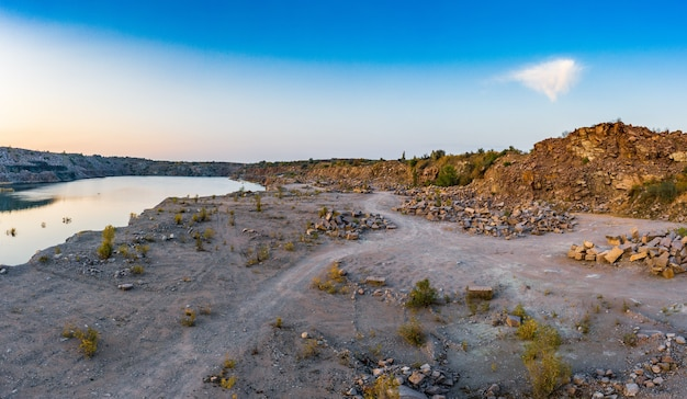 Old flooded stone quarry with large stones in the evening warm bright light covered with small dry plants in picturesque ukraine