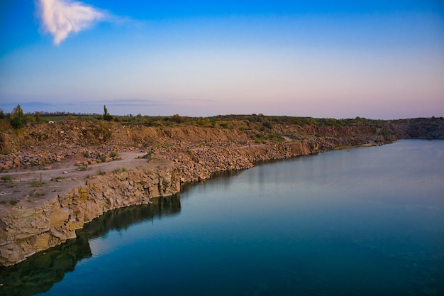 Old flooded stone quarry with large stones in the evening warm bright light