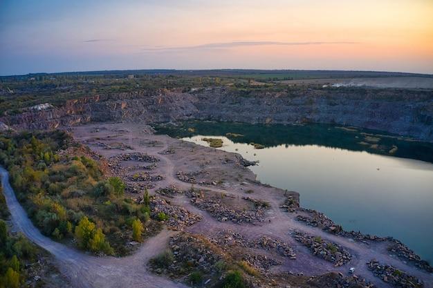 Старый затопленный каменный карьер с большими камнями в вечернем теплом ярком свете залился мелкими сухими растениями в живописной украине.