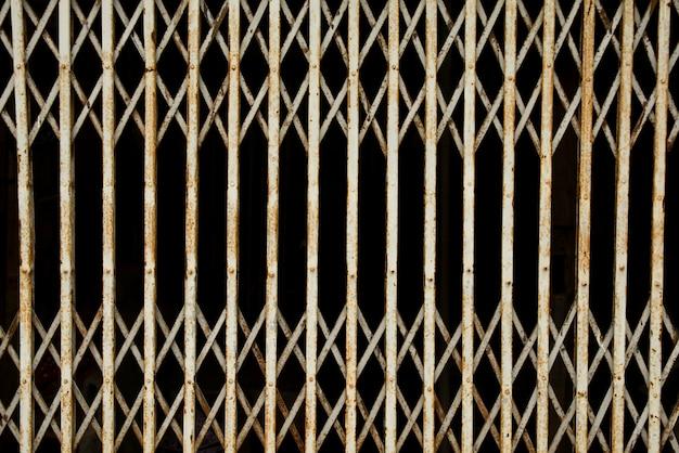 오래 된 접는 금속 문 게이트입니다. 오래 된 녹슨 철 슬라이드 도어