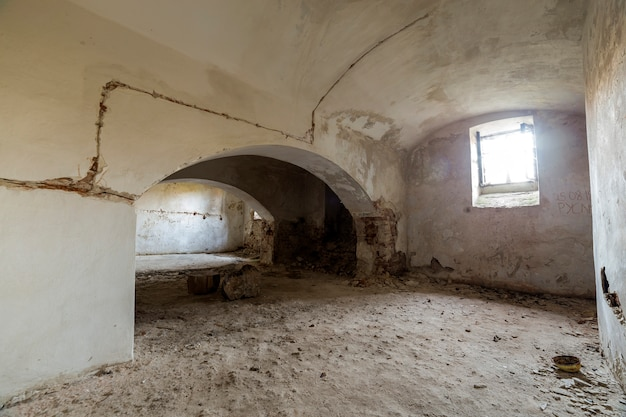 Old forsaken empty basement room of ancient building or palace with cracked plastered brick walls, low arched ceiling, small windows with iron bars and dirty floor.