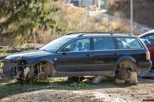 フィールドに放棄された屋外の冬の日に雪で覆われた木製のスタンプに車輪なしのクラッシュ事故後の古い見捨てられたさびた壊れたゴミ車