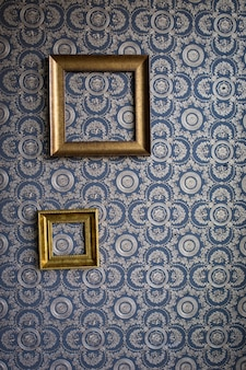 Old frame made of gypsum, on blue wallpaper