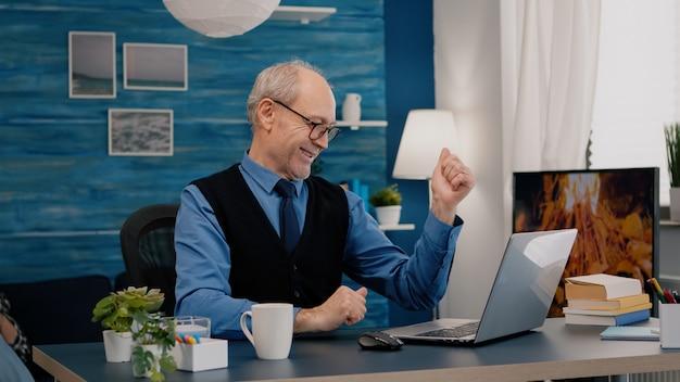 リビングルームに座って自宅でラップトップの良いニュースを受信する古いフリーランサー。現代の技術を使用して熱狂的なシニア従業員は、タイピングを読んで、シニア妻がソファに座っている間に検索します