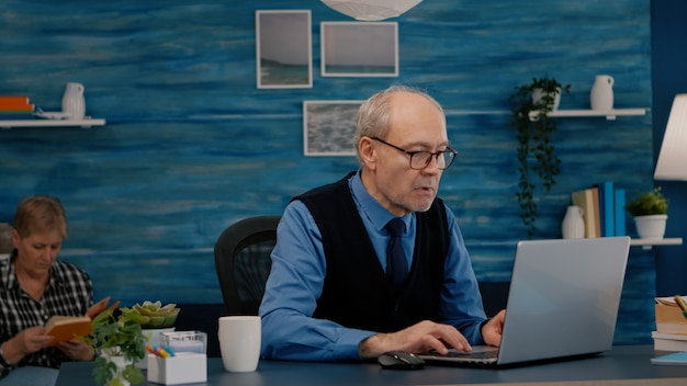 Old freelancer typing on laptop sitting in living room working remote
