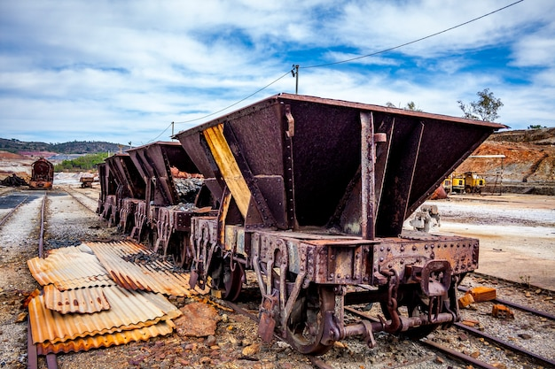 Old freight cars under a blue sky with clouds