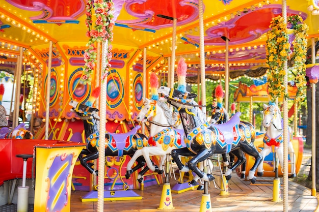 Old french carousel in a holiday park. three horses on a traditional fairground vintage carousel. merry-go-round with horses.