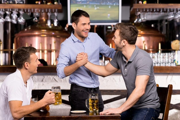 Old friends meeting. three cheerful friends meet each other in beer pub