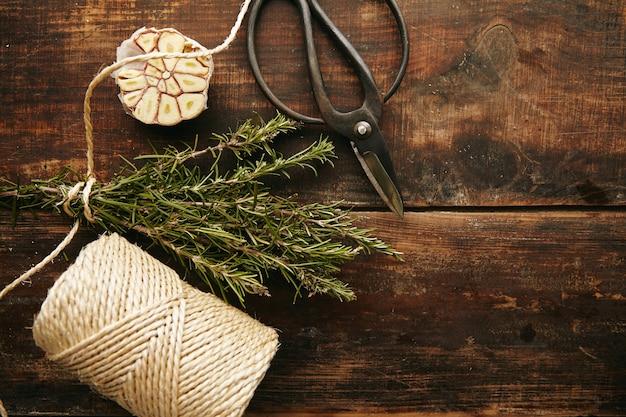 Старые садовые ножницы, толстая веревка и розмарин на деревянном столе гранж. вид сверху.