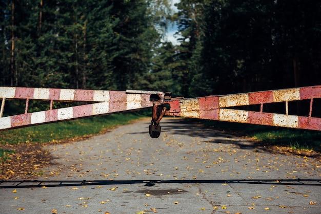 오래된 게이트는 숲으로 이어지는 도로를 차단합니다. 보호 구역, 출입 금지, 통행 금지. 자물쇠가있는 숲의 빨간색과 흰색 장벽