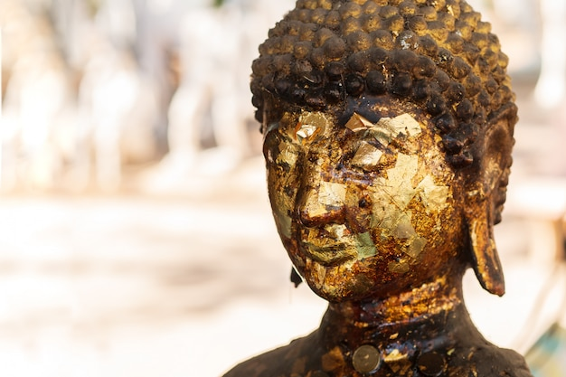 Old golden buddha on blurred