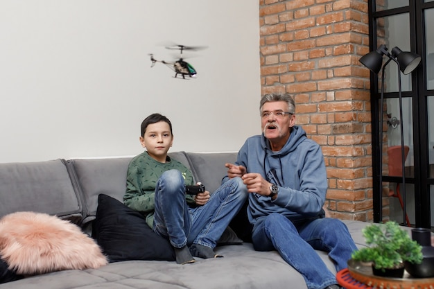 Old grandfather and cute little boy grandson play electronic toy plane lay on sofa, funny small grandkid having fun with grandpa fly on airplane laughing at home.