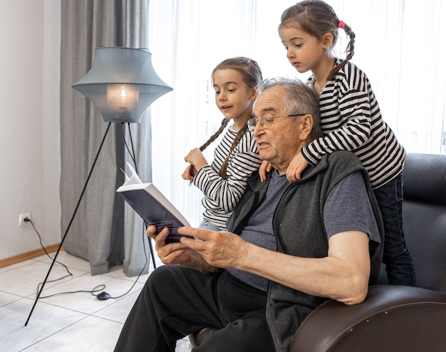 An old grandfather with glasses is reading a book to his granddaughters in his home chair.