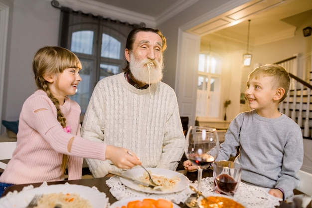 Old grandfather with his two grandchildren sitting at the kitchen table and eating pasta. little girl and boy feeding grandfather with pasta and laughing. happy lifestyle family moments.