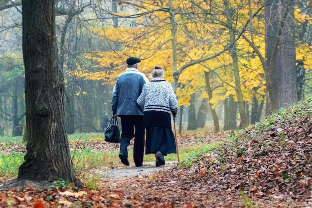 秋の公園を歩いている古い祖父母。成人期の愛。