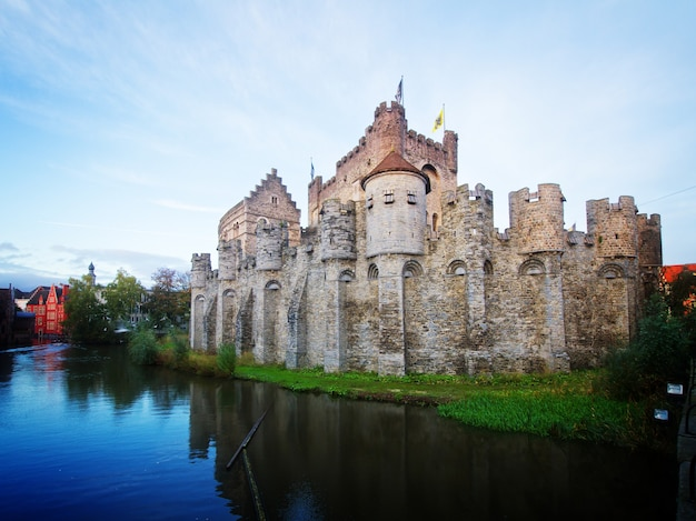 Old gravensteen castle over canal waters, ghent, belgium, retro toned