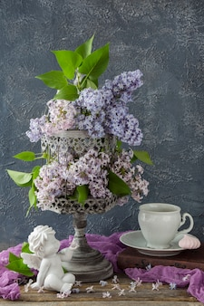 Old gray cage and in it a bouquet of lilac, a book, a cup, a meringue and a statue of a white angel