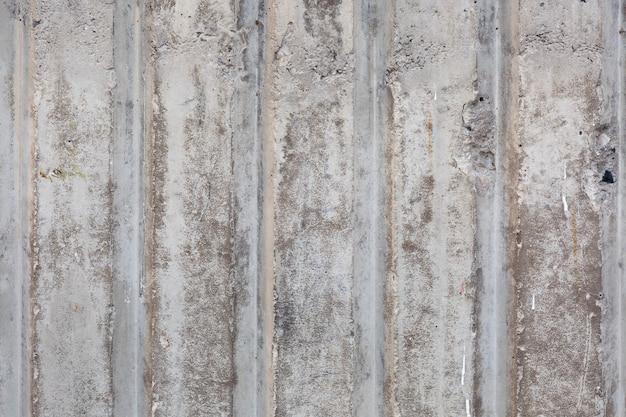 垂直線と粗いテクスチャのセメント壁の古い灰色の傷の表面