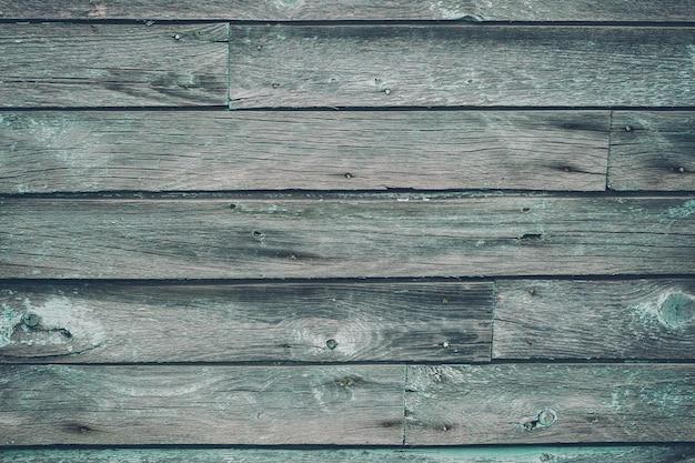 ひびの入った背景を持つ古い灰色のぼろぼろの木製の板