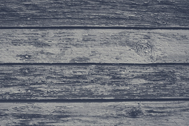 Old gray shabby wooden planks with cracked color paint