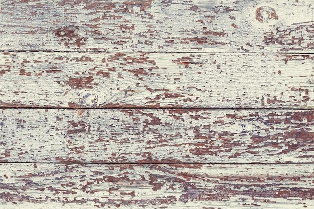 ひびの入った色の塗料で古い灰色のぼろぼろの木製の板