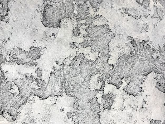 Old gray wall covered with shabby uneven plaster. texture of vintage silver stone surface, closeup.